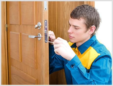 worker repairing a home front door lock